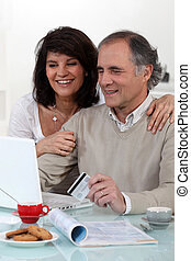 Middle-aged couple sat at computer with credit-card