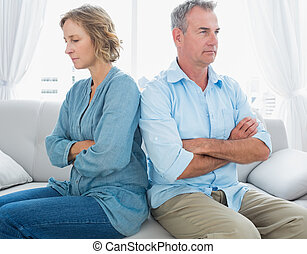 Middle aged couple sitting on the couch not speaking after a...