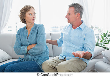 Middle aged couple sitting on the sofa having a dispute at home in the living room