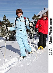 Middle-aged couple skiing to stay fit
