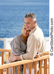 Middle aged couple stood on balcony overlooking the sea