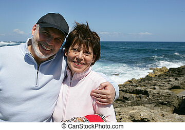 Middle-aged couple taking a walk on the beach