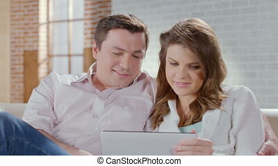 Middle-aged couple talking, laughing, viewing photos on tablet