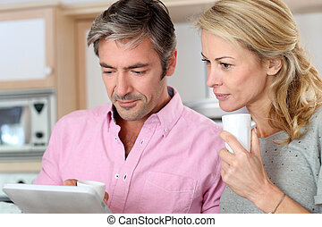 Middle aged couple using tablet in kitchen