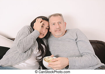 Middle-aged couple watching a scary movie
