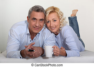 Middle-aged couple watching television