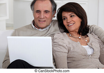 Middle-aged couple with laptop sat on sofa