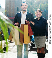 couple with shopping bags at street