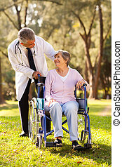 doctor pushing happy senior patient in wheelchair outdoors