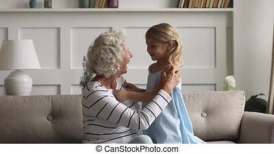 Middle aged elderly hoary woman tickling little preschool ...