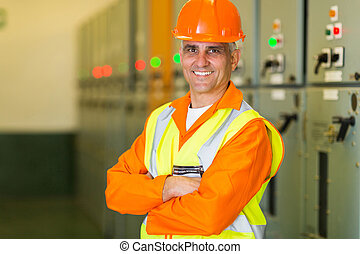 middle aged electrical engineer with arms crossed at control roo