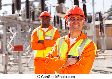 middle aged electrical worker with colleague on background