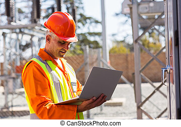 middle aged engineer using laptop in substation