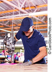 middle aged factory worker using fabric cutter - skilled...