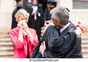 middle aged father hugging daughter at graduation
