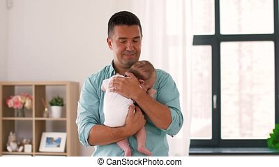 middle aged father with baby daughter at home - family,...