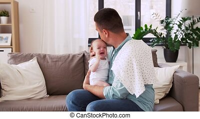 middle aged father with crying baby at home - family,...