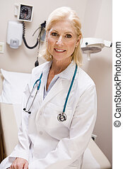 Middle Aged Female Doctor Sitting In A Hospital Ward
