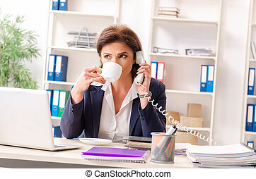 Middle-aged female employee sitting at the office