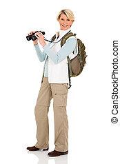 middle aged female tourist holding binoculars