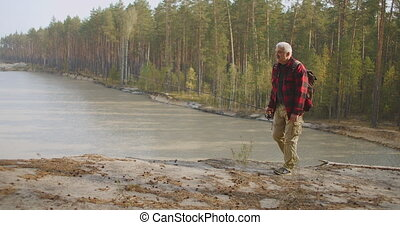 middle-aged fisherman is walking over high shore of reservoir or natural lake in forest, angling in freshwater, relax and recreation at nature in autumn day