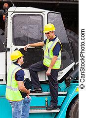 forklift driver talking to co-worker - middle aged forklift ...