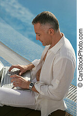 middle-aged gentleman sitting on swimming pool edge with laptop