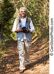 middle aged hiker walking in forest
