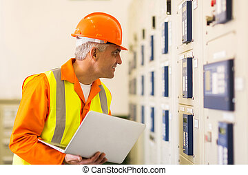 middle aged industrial electrician working in control room