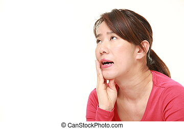 middle aged Japanese woman suffers from toothache