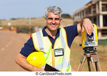 middle aged land surveyor outdoors - middle aged land...