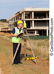 middle aged land surveyor working at construction site