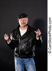 Middle-aged male dressed in leather posing as biker in ...