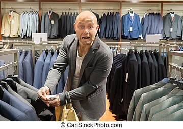 Middle-aged man amazed by jacket price in shopping mall