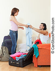 man and woman together with luggage leaving the home