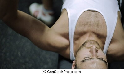 middle-aged man athlete completes the exercise on biceps muscles of hands, lying on a bench in the hall for training and muscle loading two huge rubberized dumbbells
