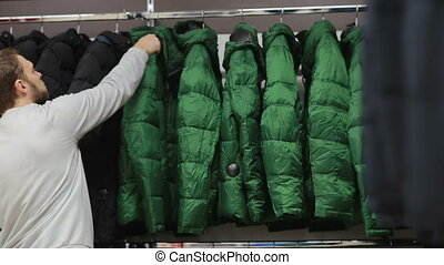 Middle-aged man chooses a warm jacket in store