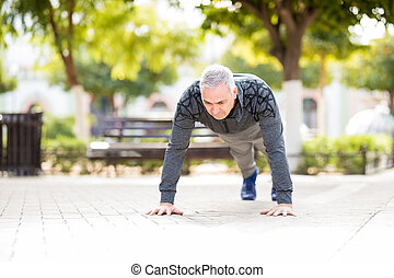 Middle aged man doing warm up exercise in the park