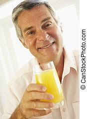 Middle Aged Man Drinking A Glass Of Orange Juice
