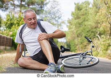Middle aged man fallen off of his bicycle