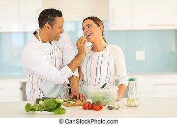 middle aged man feeding wife a piece of cucumber