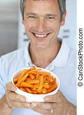 Middle Aged Man Holding A Bowl Of Carrots