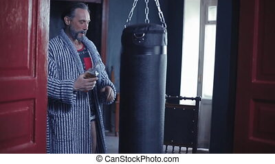 Middle-aged man in a robe walks up to a boxing pear, drinks whiskey from a bottle, smokes a cigarette and walks away. Against a healthy lifestyle concept. Alcohol and cigarettes instead of sports. . High quality FullHD footage.