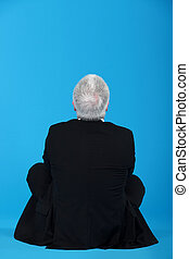 middle-aged man in lotus position with his back turned to camera