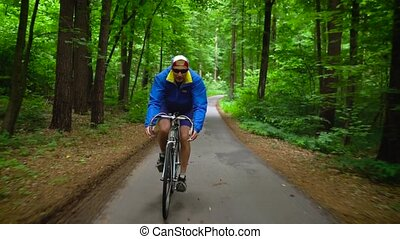 Middle-aged man is riding a road bike along a forest road