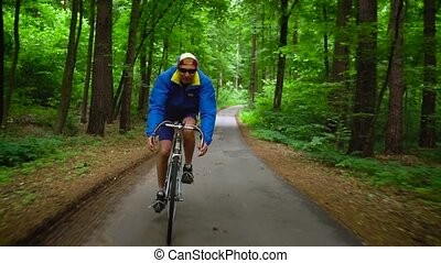 Middle-aged man is riding a road bike along a forest road,...