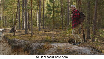 middle-aged man is walking on high shore of river in forest at autumn day, ecotourism and fishing at travel and vacation, calmness landscape of nature
