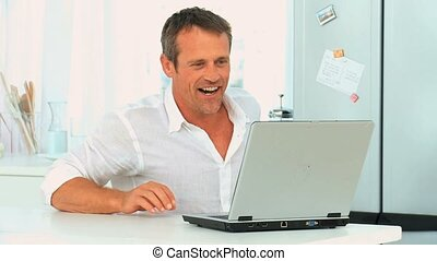 Middle aged man laughing with his laptop