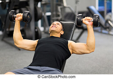 middle aged man lifting weights in gym