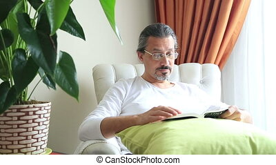 Middle aged man on couch reading book - Middle aged man...